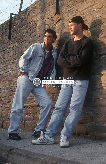Two youths leaning against a wall looking bored,