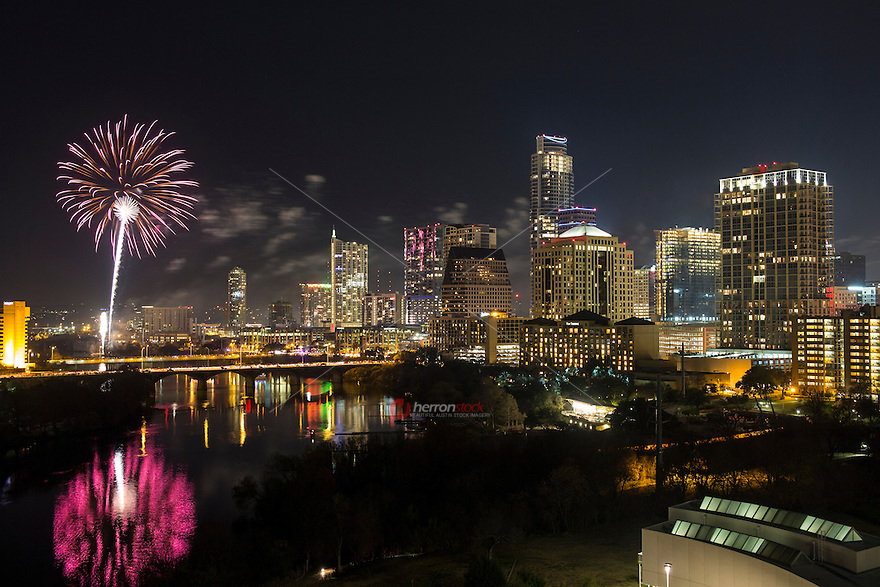Austin Texas starts the new year with fireworks streaming over the downtown skyline and the Congress Avenue Bridge reflection on Lady Bird Lake.