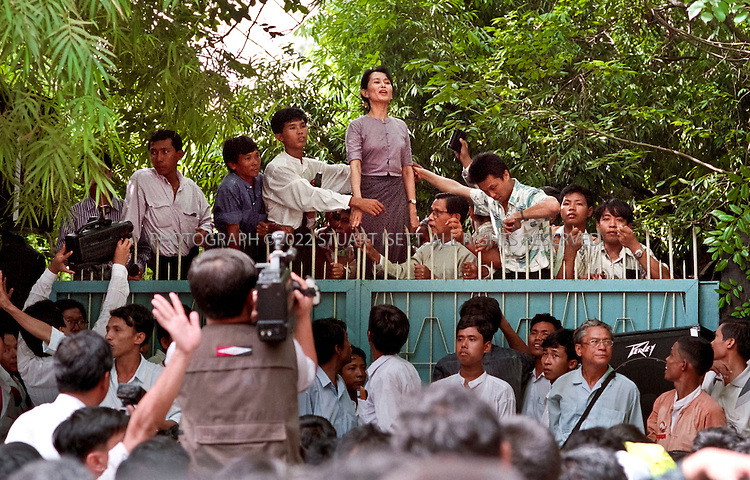 7/11/1995--Yangon, Myanmar (Rangoon, Burma)..Aung San Suu Kyi makes her first public appearance after 5 years of house arrest, at the front gate to her family compound at 54 University Avenue. As news spread of the Nobel Peace prize winner's release, nearly 10,000 ordinary citizens risked arrest to come greet her...Aung San Suu Kyi (born 19 June 1945) is a Burmese opposition politician and a former General Secretary of the National League for Democracy (NLD). In the 1990 general election, Aung San Suu Kyi's National League for Democracy party won 59% of the national votes and 80% (392 of 492) of the seats in Parliament, leading some to claim that this implies Suu Kyi was elected Prime Minister. She had, however, already been detained under house arrest before the elections. She has remained under house arrest in Myanmar for almost 14 out of the past 20 years...Aung San Suu Kyi was the recipient of the Rafto Prize and the Sakharov Prize for Freedom of Thought in 1990 and the Nobel Peace Prize in 1991. In 1992 she was awarded the Jawaharlal Nehru Award for International Understanding by the Government of India. Aung San Suu Kyi is the third child and only daughter of Aung San, considered to be father of modern-day Burma...All photographs ©2010 Stuart Isett.All rights reserved. This image may not be reproduced without expressed written permission from Stuart Isett.