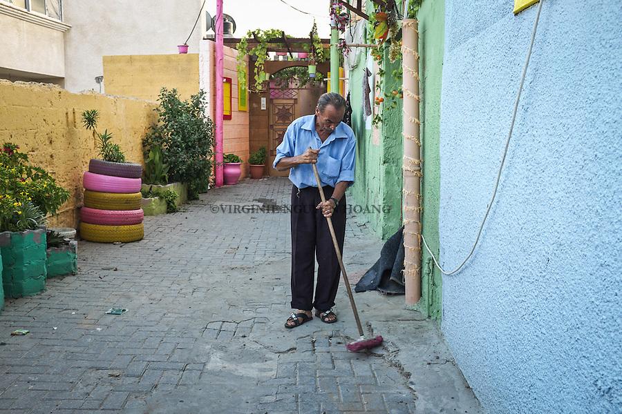GAZA, Zaytoun: the neighbour of Mohammed Al Saedy is sweeping the front of his house. To keep clean is part of the initiative. 08/15/15<br /> <br /> GAZA , Zaytoun :le voisin de Mohammed Al Saedy balaie le devant de sa maison. Garder le quartier propre fait partie de l'initiative. 15/08/15