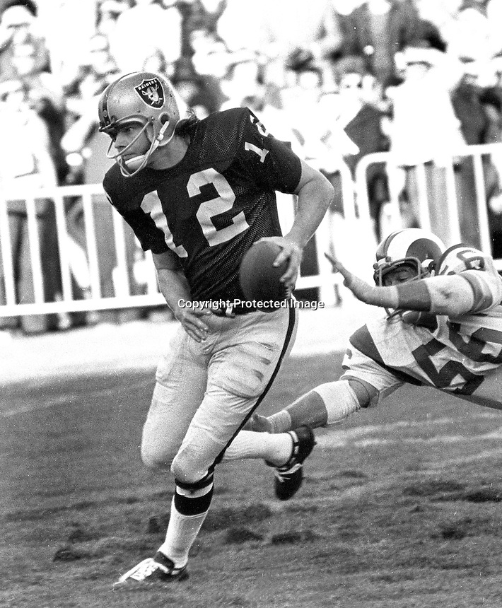 Oakland Raiders Kenny Stabler scrambles away from Ram defender..(1972 photo/Ron Riesterer)