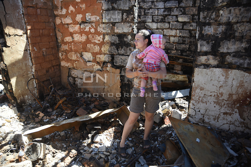 A woman holding her child in remains of her house, Donetsk, Eastern Ukraine, 21 May, 2015