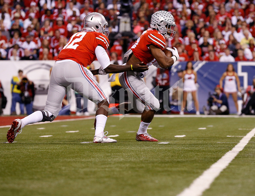 Ohio State Buckeyes quarterback Cardale Jones (12) hands off the ball to running back Ezekiel Elliott (15) during the first quarter of the Big Ten Championship game against the Wisconsin Badgers at Lucas Oil Stadium in Indianapolis on Dec. 6, 2014. (Adam Cairns / The Columbus Dispatch)