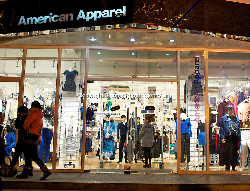 People walk past an American Apparel store in Sanlitun, Beijing, China. 11-Jan-2014