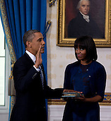 United States President Barack Obama takes the oath of office at the official swearing-in ceremony in the Blue Room of the White House Sunday, Jan. 20, 2013. Administering the oath is Supreme Court Chief Justice Roberts. Holding the bible is First Lady Michele Obama and looking on are Obama children Sasha and Malia.   .Credit: Doug Mills / Pool via CNP