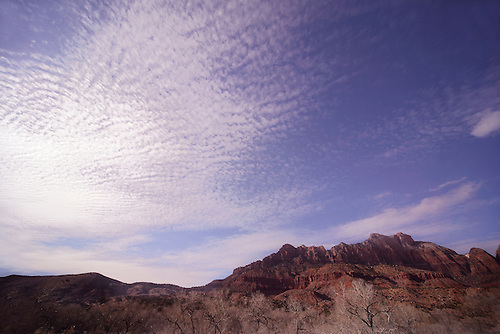 A patchwork of clouds dominates the sky during sunset at Zion Canyon at Zion National Park, Utah