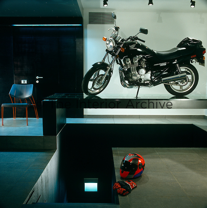 A spotlit motorbike takes pride of place in the entrance hall of the property
