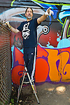 """Huntington, New York, U.S. 24th August 2013. SONIC BAD, legendary street artist JESSE RODRIGUEZ from the Bronx, is on a step ladder graffiti painting the """"Art Matters"""" wall, on the back of the Huntington Arts Council building, during the the art event """"Off the Walls"""" Block Party, by SPARKBOOM, a project the council created to help emerging artists, showcase talents, and help its artistic family network."""