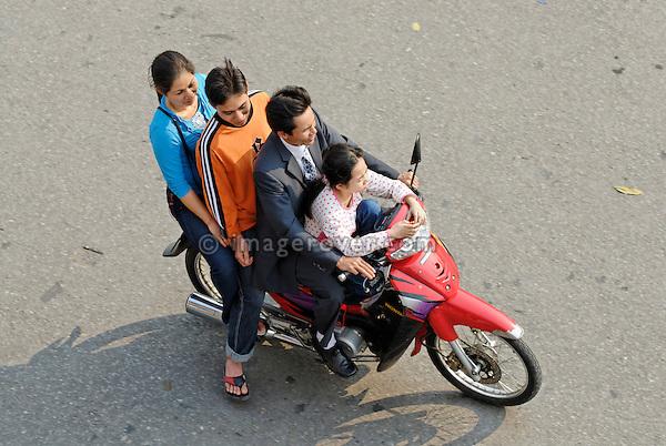 Asia, Vietnam, Hanoi. Hanoi old quarter. Vietnamese family of four riding on a motorbike through Hanoi.