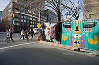 Pedestrians pass construction containers at East Fourth Street and the Bowery decorated with graffiti style street art in the trendy East Village neighborhood of New York on Saturday, January 28, 2012. (© Richard B. Levine)