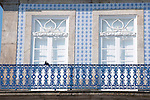 Two windows in Porto, Portugal with a blue iron balcony and blue and white tiles.
