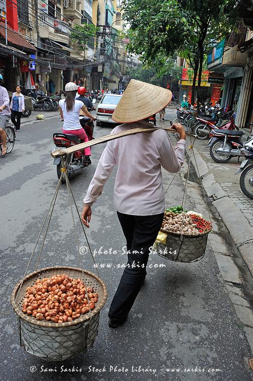Woman carrying baskets of fruits, Hanoi, Vietnam