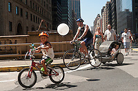 New York, NY -  15 August 2009 - Family with one child riding his own bike decorated with pin wheels, and two younger children towed a trailer, round the turn on the Grand Central Viaduct. Summer Streets, the second of three car free Saturdays where the City's Department of Transportation (DOT) closes almost seven miles of traffic for pedestrians, cyclists, and skaters. The Car-Free event opened up almost 7 miles of car-free streets along Centre Street, Lafayette Street, Fourth Avenue and Park Avenue, from the Brooklyn Bridge to 72nd Street and Central Park