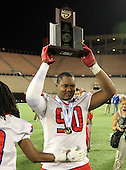 Manatee Hurricanes defensive lineman DeMarcus Christmas #90 hoists the Championship trophy after the Florida High School Athletic Association 7A Championship Game at Florida's Citrus Bowl on December 16, 2011 in Orlando, Florida.  Manatee defeated First Coast 40-0.  (Photo By Mike Janes Photography)