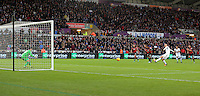 Jonjo Shelvey of Swansea (R) scores from the penalty spot against Bournemouth goalkeeper Adam Federici who took the penalty during the Barclays Premier League match between Swansea City and Bournemouth at the Liberty Stadium, Swansea on November 21 2015