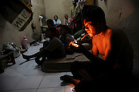 "30 year old Pak Sutrisno lights a cigarette in the ""home"" he and his family of six inhabit in the market complex of Porong Town. A former resident of the now completely submerged Renokonongo village, Sutrisno was a rice farmer who has lost his land and his income in the mud flow disaster. Since May 2006, more than 10,000 people in the Porong subdistrict of Sidoarjo have been displaced by hot mud flowing from a natural gas well that was being drilled by the oil company Lapindo Brantas. The torrent of mud - up to 125,000 cubic metres per day - continued to flow three years later."