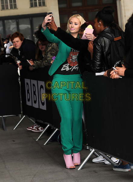 Iggy Azalea<br /> At BBC Radio 1, London, England.<br /> May 31st, 2013<br /> full length green suit black top print pink open toe boots posing fans crowd taking picture photograph camera <br /> CAP/AOU<br /> &copy;AOU/Capital Pictures