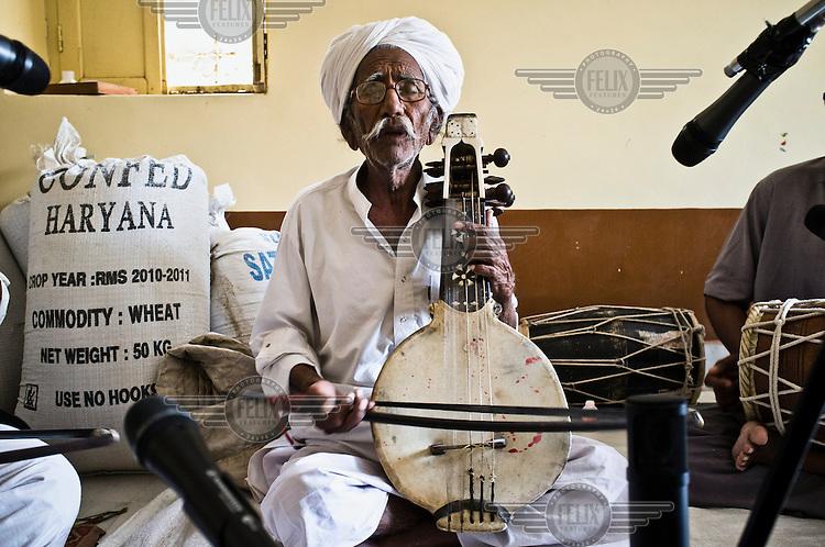 75 year old Manganiyar folk musician, Saqar Khan, plays the Kamancha (a stringed instrument of Persian origins played with a bow) at his home in Hamira Village.