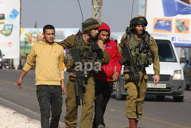 Israeli soldiers detain Palestinian youths in a protest to block a road leading to Huwwara checkpoint near the West Bank city of Nablus during a demonstration in support of the people of the Gaza Strip and against Israeli air strikes on November 15, 2012. Several Palestinians were killed following a series of Israel's concurrent airstrikes on Gaza city, among them was Ahmed al-Jaabari, top commander of Hamas armed wing Al-Qassam brigades, and more than 150 others wounded, government's emergency services in the Gaza Strip said. Photo by Nedal Eshtayah