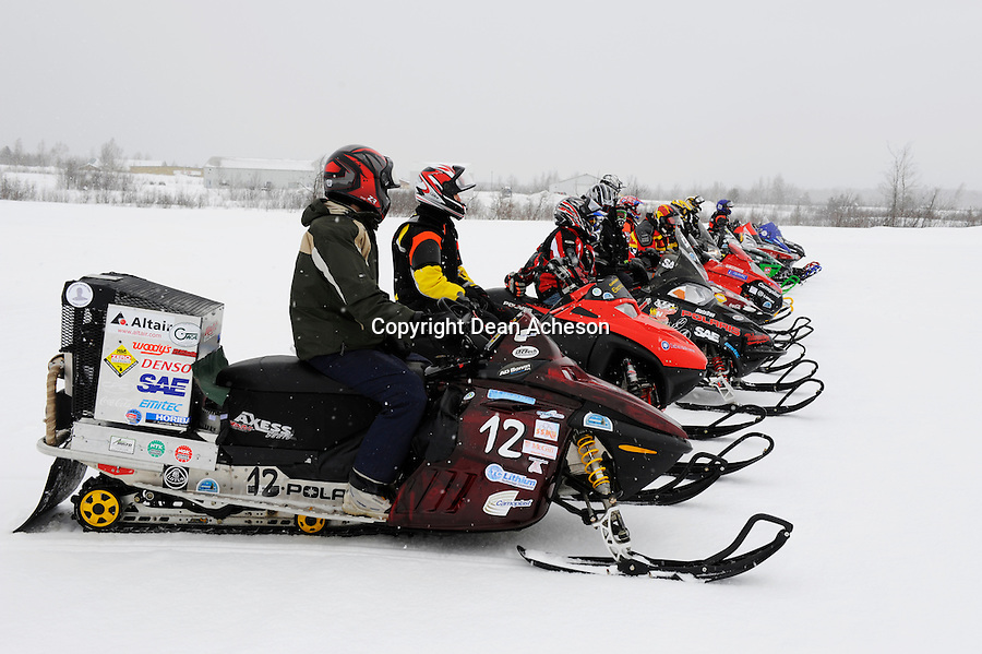 Competitors, including battery-powered sleds, wait their turns to run their sleds in the acceleration event during the 2008 SAE Clean Snowmobile Challenge, a competition among US and international universities to develop a prototype snowmobile that meets the 2012 standards for exhaust emissions and noise output. The Society of Automotive Engineers' ninth annual event culminated with an acceleration and handling competition held Saturday, March 15 at Keweenaw Research Center, just outside of Houghton, Mich. Unlike last year's competition that saw muddy track conditions, this year's competitors had just light snow flurries as well as excellent track conditions. the event was hosted by Michigan Technological University. No. 12 was an entry from McGill University, Montreal, Quebec.