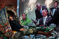 A Bangladeshi rickshaw puller takes a nap on his rickshaw next to a banner printed portraits of American President Barack Obama, right, and Bangladeshís Prime Minister Sheikh Hasina, left, on a road in Dhaka, Bangladesh.