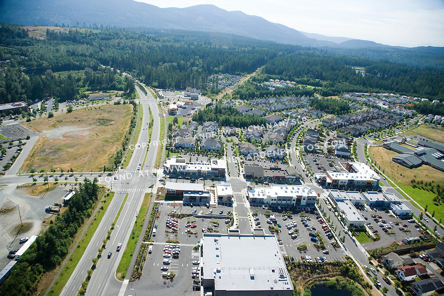 A late afternoon summer aerial photo of Snoqualmie Ridge, a large master-planned community of homes and businesses roughly 20 miles east of Seattle nestled in the foothills of the Cascade Mtns.