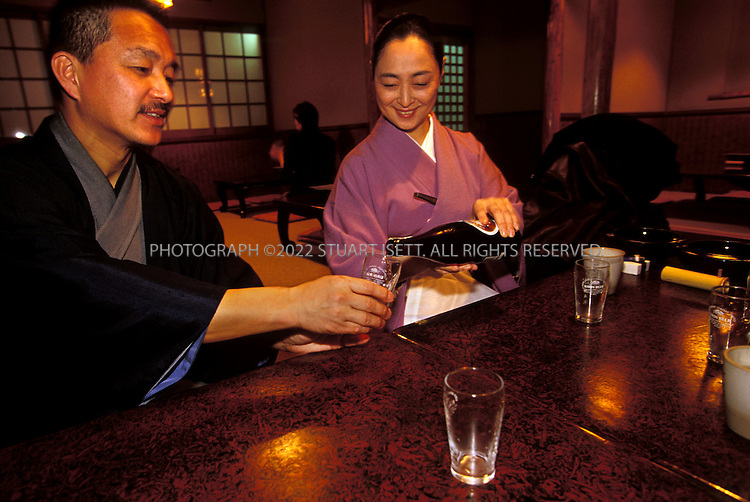 Kyoto, Japan..Mineko Iwasaki pours a beer for her husband Junichiro at a Gion restaurant. ..All photographs ©2003 Stuart Isett.All rights reserved.