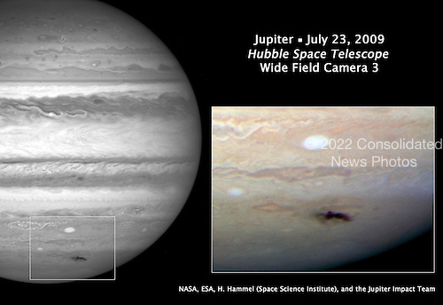 "Baltimore, MD - July 24, 2009 -- This Hubble picture, taken on July 23, 2009 is the sharpest visible-light picture taken of the impact feature. The observations were made with Hubble's new camera, the Wide Field Camera 3 (WFC3).  The combination of the Hubble data with mid-infrared images from ground-based telescopes will give astronomers an insight into changes of the vertical structure of Jupiter's atmosphere due to the impact. The expanding spot is twice the length of the United States.  First discovered by Australian amateur astronomer Anthony Wesley, the feature is the impact site and ""backsplash"" of material from a small object that plunged into Jupiter's atmosphere and disintegrated.  The only other time in history such a feature has been seen on Jupiter was in 1994 during the collision of fragments from comet Shoemaker-Levy 9. The spot looks strikingly similar to comet Shoemaker-Levy 9's impact features. The details seen in the Hubble view shows lumpiness in the debris plume caused by turbulence in Jupiter's atmosphere.  The impactor is estimated to be the size of several football fields. The force of the explosion on Jupiter was thousands of times more powerful than the suspected comet or asteroid that exploded in June 1908 over the Tunguska River Valley in Siberia.  This is a natural color image of Jupiter as seen in visible light..Credit: NASA-ESA-STSci via CNP"