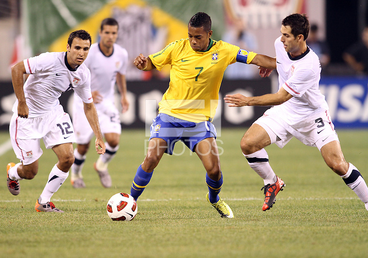 Jonathan Bornstein #12 and Carlos Bocanegra #3 of the USA close in on Robinho #7 of Brazil during an international friendly match in Giants Stadium, on August 10 2010, in East Rutherford, New Jersey. brazil won 2-0.