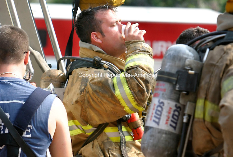 WATERBURY, CT. 10 July 2006-071006SV04-- Firefighters drink water in rehab after extinguishing an apartment fire at 201 East Main St. in Waterbury early Monday.<br /> Steven Valenti Republican-American