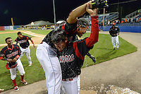 Batavia Muckdogs outfielder Victor Castro (40) is lifted over the shoulders of Josh Hodges (44) after a walk off hit and the water bucket being dumped over them during a game against the Brooklyn Cyclones on August 11, 2014 at Dwyer Stadium in Batavia, New York.  Batavia defeated Brooklyn 4-3.  (Mike Janes/Four Seam Images)