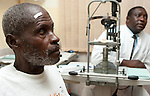 After being diagnosed with Macular Degeneration which causes sever catarct a patient waits for surgery at the Crystal Eye Clinic in Accra, Ghana. The white tape over the patient's right eye identifies the eye that will be operated on.