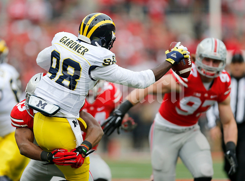 Ohio State Buckeyes linebacker Darron Lee (43) brings down Michigan Wolverines quarterback Devin Gardner (98) during the first quarter of the NCAA football game against Michigan at Ohio Stadium on Saturday, November 29, 2014. (Columbus Dispatch photo by Jonathan Quilter)