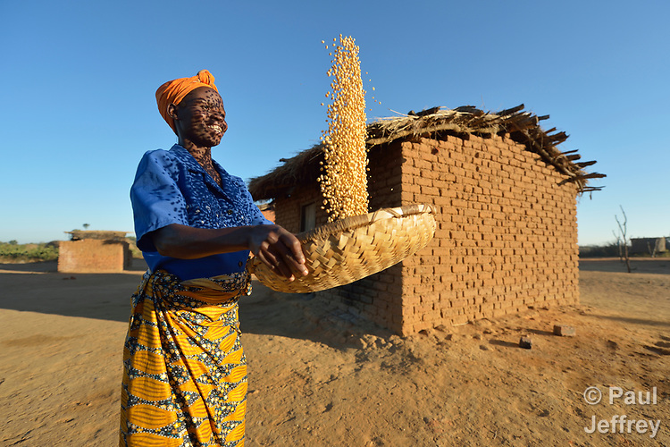 Frances Mtonga winnows corn in Chibamu Jere, Malawi. Pregnant for the third time, Mtonga and other women in the village get support from the Maternal, Newborn and Child Health program of the Livingstonia Synod of the Church of Central Africa Presbyterian. Her husband works in South Africa and sends home money to support her and her children.