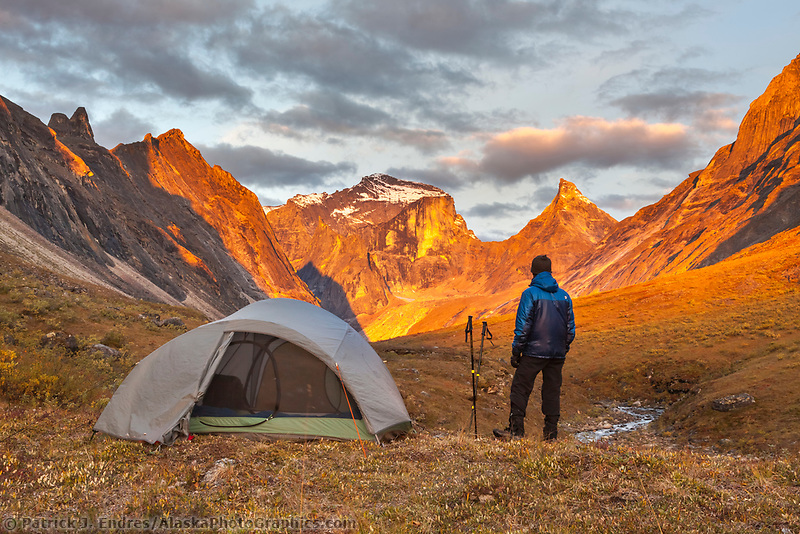 Camper watches a brilliant sunrise from a mountain ridge in the Arrigetch Peaks, Gates of the Arctic National Park, Alaska.