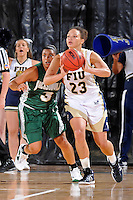 11 November 2011:  FIU's Finda Mansare (23) passes the ball while being defended by Jacksonville's Jessica George (3) in the first half as the FIU Golden Panthers defeated the Jacksonville University Dolphins, 63-37, at the U.S. Century Bank Arena in Miami, Florida.