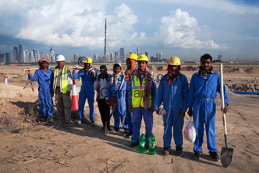 United Arab Emirates, Dubai: Development near Nad Al Sheba showing Asian workers, city skyline and the Burj Dubai