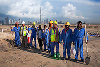 United Arab Emirates, Dubai: Development near Nad Al Sheba showing Asian workers, city skyline and the Burj Dubai
