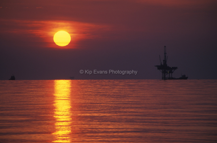 An off-shore oil rig at sunset.