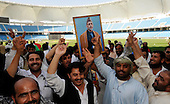 Afghanistan V UAE - World T20 Super Four stage qualifying cricket match in Dubai Sports City Cricket Stadium - Afghanistan fans, waving a placard image of Afghan President Hamed Karzi celebrate after their team beat the UAE by 4 wickets, thereby qualifying for the World T20 in the West Indies in April and May - Picture by Donald MacLeod 13.02.10