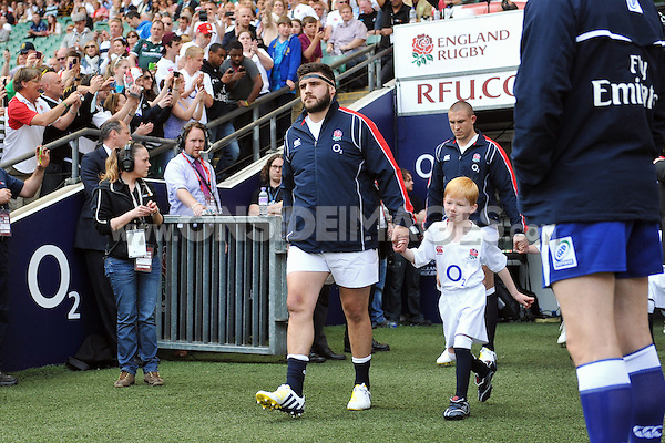 England captain Rob Webber, mascot in hand, leads the team onto the field. Killik Cup International match between England and the Barbarians on May 26, 2013 at Twickenham Stadium in London, England. Photo by: Patrick Khachfe / Onside Images