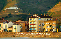 the name of the town painted in large white letters and a sign with Ermitage Chapoutier. Houses along the river. The Hermitage vineyards on the hill behind the city Tain-l'Hermitage, on the steep sloping hill, stone terraced. Sometimes spelled Ermitage. Tain l'Hermitage, Drome, Drôme, France, Europe
