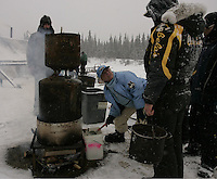 Jeff King waits in line as Dee Dee Jonrowe gets hot water for her dogs at  the Nikolai checkpoint