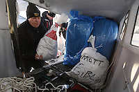 "February 16, 2013  Iditarod Air Force pilot Mike Swalling loads his plane with straw and musher's food bags headed for the Skewnta checkpoint at the Willow airport on the first day of the ""Food Fly""...Iditarod 2013 Photo Copyright Jeff Schultz  -- Do not reproduce without written permission"