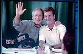 New York, NY - September 1, 2004 --   United States President George W. Bush waves to at the 2004 Republican Convention in Madison Square Garden in New York, New York on Wednesday, September 1, 2004 from a firehouse in Elmhurst, Queens, New York.   The photo was taken from the main viewing screen in the convention hall.  The man at right is unidentified..Credit: Ron Sachs / CNP.(RESTRICTION: No New York Metro or other Newspapers within a 75 mile radius of New York City)