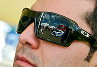Grand-Am driver Memo Rojas' race car is reflected in his sunglasses in the paddock at Watkins Glen Internationa Raceway, Watkins Glen, NY, August 6, 2010.  (Photo by Brian Cleary/www.bcpix.com)