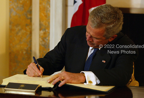 "Washington, D.C. - July 8, 2005 -- President George W. Bush signs the book of condolences at the British embassy in Washington, DC as Ambassador Sir David Manning looks on.  The President stated: ""Yesterday was an incredibly sad day for a lot of families in London.  It's my honor, Ambassador, to come and represent our great country in extending our condolences to the -- to the people of Great Britain.  To those who suffer loss of life, we pray for God's blessings.  For those who are injured, we pray for fast healing.  The British people are steadfast and strong.  Long we've admired the great spirit of the -- of Londoners and the people of Great Britain.  Once again that great strength of character is coming through.""<br /> Credit: Dennis Brack - Pool via CNP"