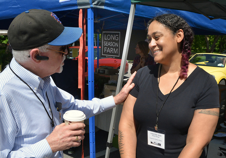 John Bassler, of the Market Committee, talks with the Market Manager, Christine Moss, on duty at the Opening Day of the 2017 Saugerties Farmer's Market on Saturday, May 27, 2017. Photo by Jim Peppler. Copyright/Jim Peppler-2017.