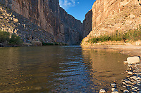 The mouth of Santa Elena Canyon as the waters of the Rio Grande river flow down stream towards the coast early morning with a morning glow. Another Texas landscape with these mountains separated by the Rio Grande with the US side on the right and Mexico on the left in Big Bend National Park.