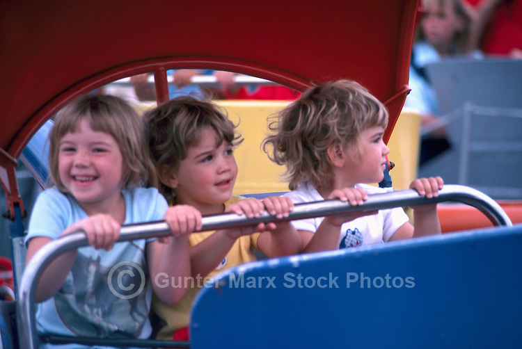 Three Young Children sitting in Amusement Ride and holding on to Safety Bar, at the Pacific National Exhibition (PNE), Vancouver, BC, British Columbia, Canada (No Model Release Available)